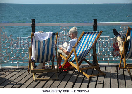 Brighton, UK - September 1 2018: People bask in the sun on the Brighton Palace Pier on a sunny afternoon on 1​ September 2018.   The Pier, in the central waterfront section, opened in 1899 houses amusement rides as well as food kiosks. Credit: David Mbiyu /Alamy Live News - Stock Image