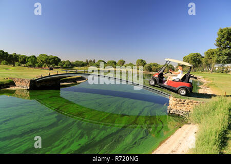 Golf cart (buggy) crossing bridge over river. - Stock Image