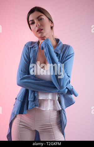 Attractive young woman in blue jeans shirt posing on pink background in studio. Woman holding hand on beard. Fashion girl portrait concept. Close up - Stock Image