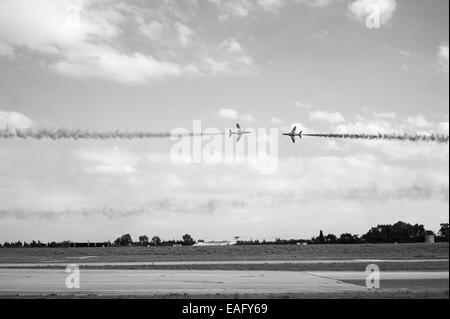 Red Arrows flying display at Malta International Airshow 2014, two aircraft cross head on - Stock Image