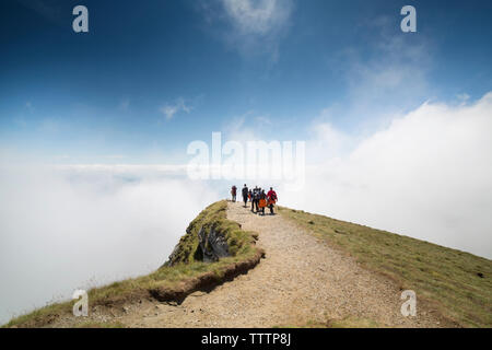 Hikers on cliff covered by clouds - Stock Image