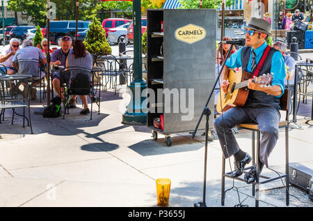 ASHEVILLE, NC, USA-10 JUNE 18:  A street performer sings and plays guitar, while patrons dine outside at Carmel's Kitchen and Bar. - Stock Image