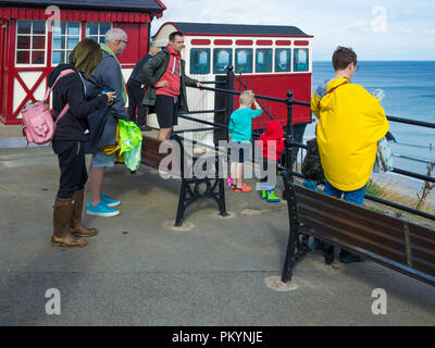 A family at the top station of the Saltburn Cliff Funicular tramway looking down at the pier - Stock Image