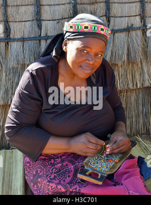 Zulu woman troupe member in traditional clothes making bead souvenirs in front a Zulu rondavel ,Shakaland Cultural - Stock Image