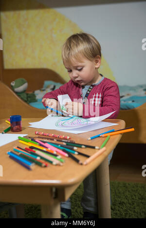 Little boy cutting a paper with scissor, Munich, Germany - Stock Image
