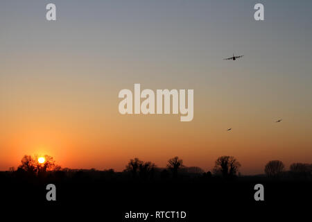 A flight of three USAF MC-130J's from the Mildenhall based 67th SOS are seen circling around to the South West of the airfield at dusk. - Stock Image