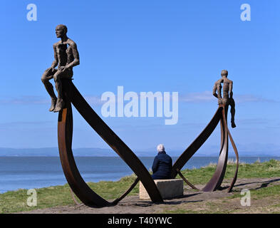Visitor at 'Ship', metal sculpture by Anna Gillespie, 2019. Half Moon Bay, Heysham, Lancashire, England, United Kingdom, Europe. - Stock Image