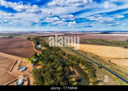 Gwydir river shallow during draught with scarse gum trees around remote single farm at the edge of cultivated plowed farm fields in flat plains around - Stock Image