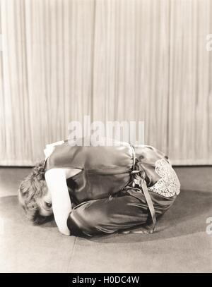Woman curled up on floor - Stock Image