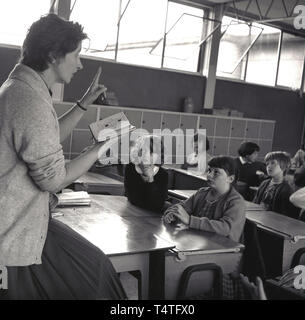 1960s, historical, female teacher in classroom with book in her hand teaching the listening school children who are sitting at small wooden desks, England, UK. - Stock Image