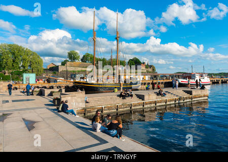 Oslo Norway, view of young people relaxing beside a quay in the harbour area (Aker Brygge) in Oslo on a summer afternoon, Norway. - Stock Image