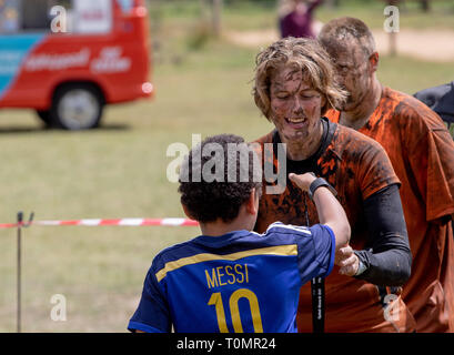 Woman mud runner getting her medal from a small boy - Stock Image
