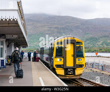 ScotRail tran at platform, Kyle of Lochalsh station, with passengers baording with suitcases, Scotland, UK - Stock Image