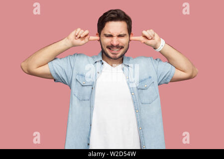 I don't want to hear you. Portrait of confused handsome bearded young man in blue casual style shirt standing and putting fingers on ears and dont car - Stock Image