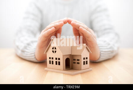 Property insurance. House miniature covered by hands. - Stock Image