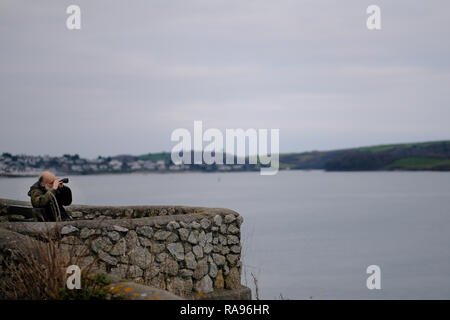 A retired man looking through binoculars/telescope at ships and birds on the sea in Cornwall, UK in winter. - Stock Image
