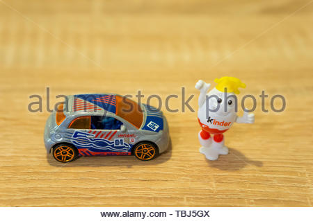 Happy Kinder egg figure standing next to a Mattel - Stock Image