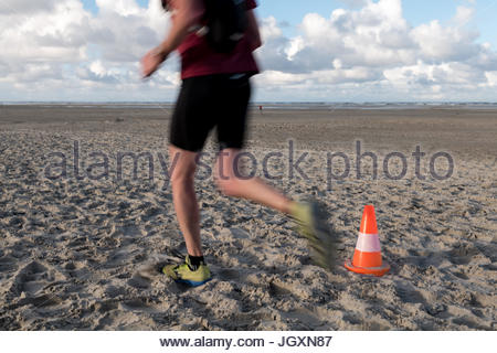 Traffic cone on sand beach with many footsteps man running - Stock Image