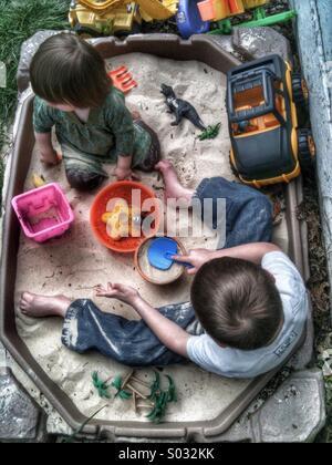 Kids in sandbox in the summer - Stock Image