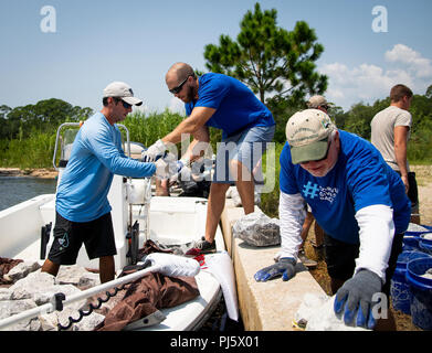 """Volunteers load rocks into a boat for a """"living shoreline"""" project Aug. 24 along the Eglin Air Force Base coastline.  The goal of the project to build an artificial reef along 1,400 linear feet of Eglin shoreline is to protect against erosion.  Volunteers from base agencies have completed 450 feet using more than 60 tons of limestone rock.  (U.S. Air Force photo/Samuel King Jr.) - Stock Image"""