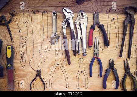 Tools hanging over sketches made on wooden wall - Stock Image