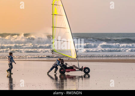 A father and his sons having fun with a Ludic Seagull sand yacht on Fistral Beach in Newquay Cornwall. - Stock Image