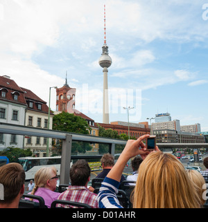 The television tower which is a popular visual landmark in the city centre of Berlin viewed by tourists on a bus - Stock Image