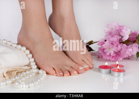 Woman bare feet with french pedicure on white towel and decoration candle, pearls and pink flower in beauty studio isolated on white background - Stock Image