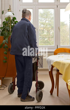 Old woman moving around in her living room with 3-wheeled walker. A mobility device for people with balance and strenght issues in small spaces. - Stock Image