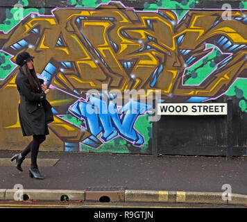Woman in black walking past colourful graffiti, in Wood street, Taunton, Somerset, South West England, UK, TA1 1UN - Stock Image