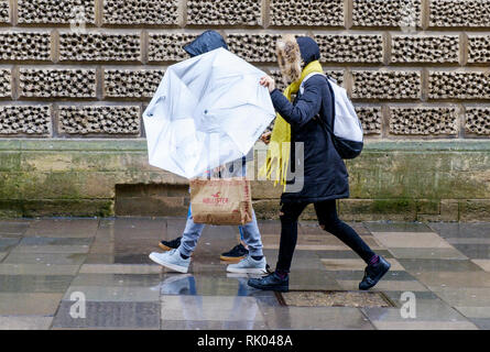 Bath, UK. 8th February, 2019. As storm Eric brings gales and heavy rain across the UK pedestrians are pictured in the centre of Bath struggling with an umbrella as they brave the heavy rain and wind. Credit: Lynchpics/Alamy Live News - Stock Image