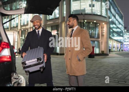 Businessmen loading suitcase into car on urban street corner at night - Stock Image