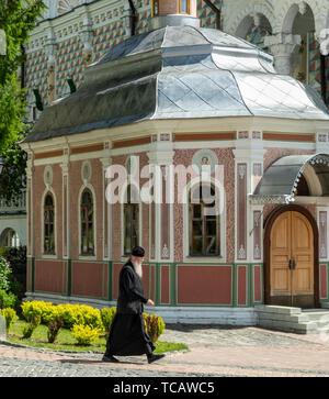 White-bearded monk crossing courtyard, Sergiyev Posad monastery, Russia - Stock Image