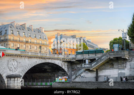 Dusk at the Pont Saint-Michel Bridge as tourists walk along the banks of the Seine River on the Ile de la Cite in Paris France. - Stock Image