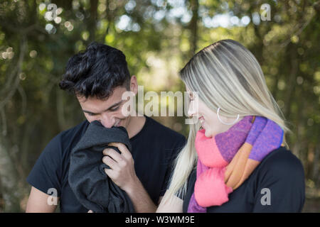 man and woman in black shirts enjoy the shade of the trees - Stock Image