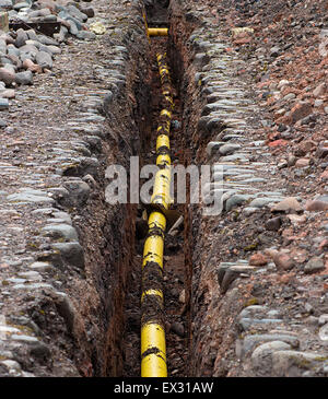 Underground services yellow Gas Polyethylene Pipe being sunk into the ground under the frost line. - Stock Image