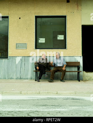 Local men chat on a bench smoking a cigarette. Valle de Ricote, Murcia, Spain. - Stock Image