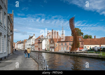 Modern metal street art displayed alongside a canal with traditional architecture in the medieval city of Bruges, West Flanders, Belgium. - Stock Image
