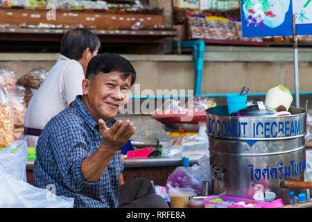 Damnoen Saduak, Thailand - August 29, 2018: Man selling coconut ice cream from a boat in Damnoen Saduak Floating Market, Ratchaburi, Thailand. - Stock Image