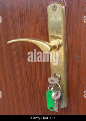 Bunch of keys in door lock and green tag close up - Stock Image