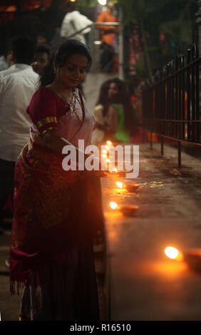 Pune, India - November 2018: A woman lights up lamp in front of a temple where many people have gathered to celebrate Diwali. - Stock Image