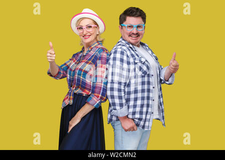 Couple of friends, adult man and woman in casual checkered shirt standing together back to back, showing thumbs up, toothy smile and looking at camera - Stock Image