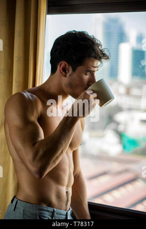 Sexy handsome young man standing shirtless in his bedroom drinking a cup of coffee or tea next to window curtains - Stock Image