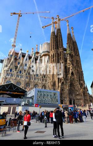 Antoni Gaudi's La Sagrada Familia basillica with crowds and construction cranes. Barcelona, Catalunya, Spain - Stock Image