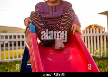 A little girl wearing striped pants and dancing on a slide. - Stock Image