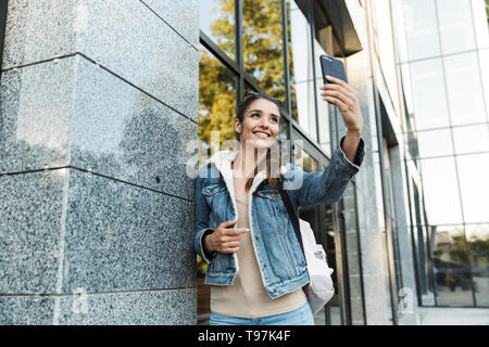 Beautiful young brunette woman wearing jacket, carrying backpack walking outdoors, taking a selfie - Stock Image