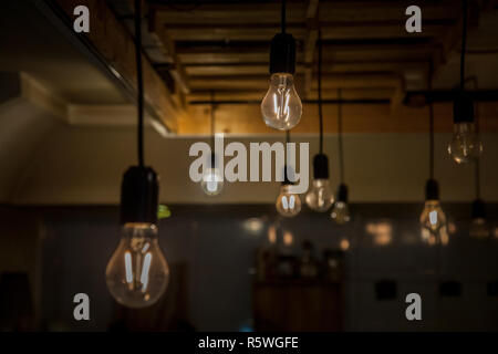 Vintage incandescence lightbulbs, with their iconic filament, hanging on the roof inside a hipsterish industrial room  Picture of lightbulbs hnging fr - Stock Image