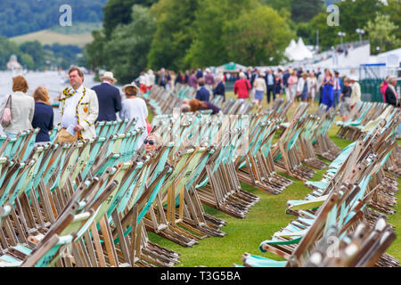 Spectators and rows of empty green canvas deckchairs labelled with HRR, at Henley Regatta, Henley-on-Thames, Oxfordshire, UK on a cold day - Stock Image