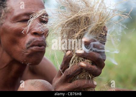 Bushman / San making fire in the Kalahari desert near Ghanzi, Botswana, Africa - Stock Image