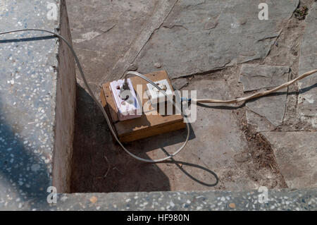 Rustic trailing power socket with a power switch, assembled on a wooden board. Myanmar (Burma). - Stock Image